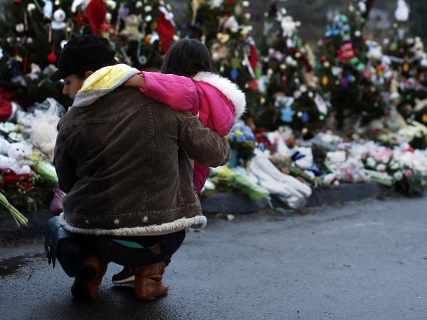 A woman and child earlier this week at a makeshift memorial in Newtown, Conn.