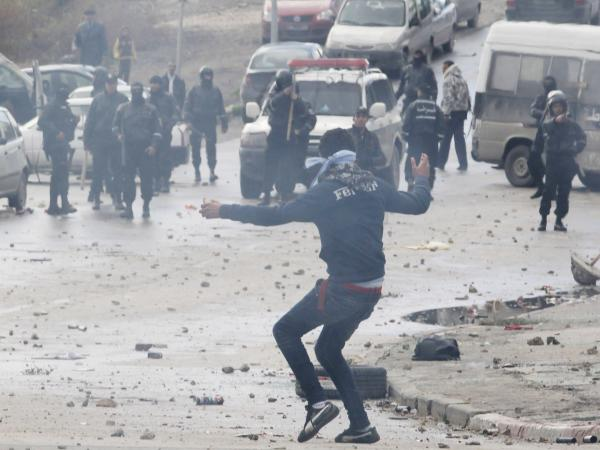 A protester, and riot police in the background, during the clashes Friday in Tunis.
