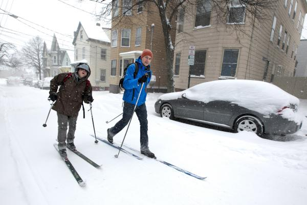 Andre Tranchemantague (left) and Will Guerette ski to a bar during the early stages of the snowstorm in Portland.