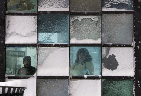 Riders wait in a bus stop where color-tinted windows collect snow during a storm in Portland, Maine. The storm sweeping into Maine already has dumped half a foot of snow around Portland, and contributed to a 19-car pileup.