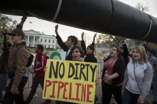 Demonstrators carry a mock pipeline as they pass the White House to protest the Keystone Pipeline, in Washington, D.C., on Nov. 18, 2012.