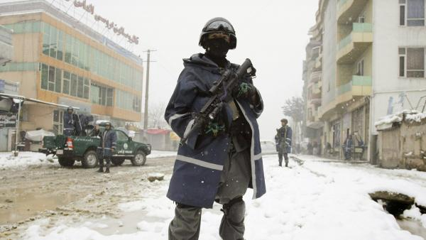 An Afghan policeman stands guard near the scene of a suicide attack in Kabul, Afghanistan, Feb. 27