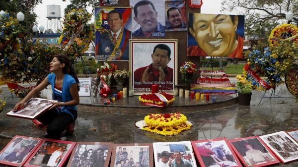A woman wipes photos of late President Hugo Chavez at a makeshift altar for him in the main square of Sabaneta, western Venezuela, on Saturday.