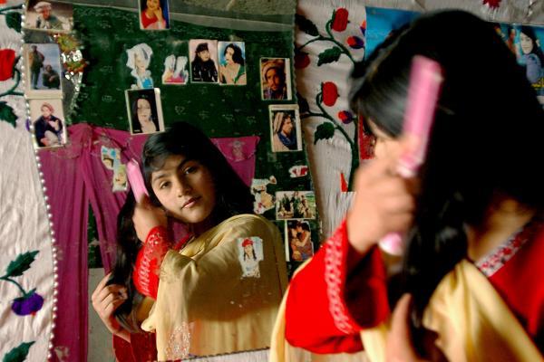 An Afghan girl brushes her hair in Kabul, 2007.