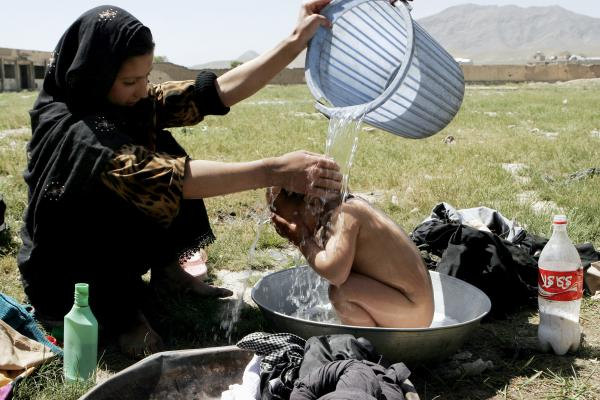 An Afghan girl bathes her brother near a building where refugees live in Kabul, 2007.