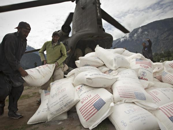 Pakistani aid workers offload USAID food supplies from an Army helicopter in Kallam Valley during catastrophic flooding in 2010.