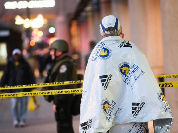 A marathon runner, wrapped in a blanket to stay warm after the race, watched Monday as authorities investigated the bombings that shook the finish line area at the Boston Marathon. At least three people were killed and dozens were wounded.