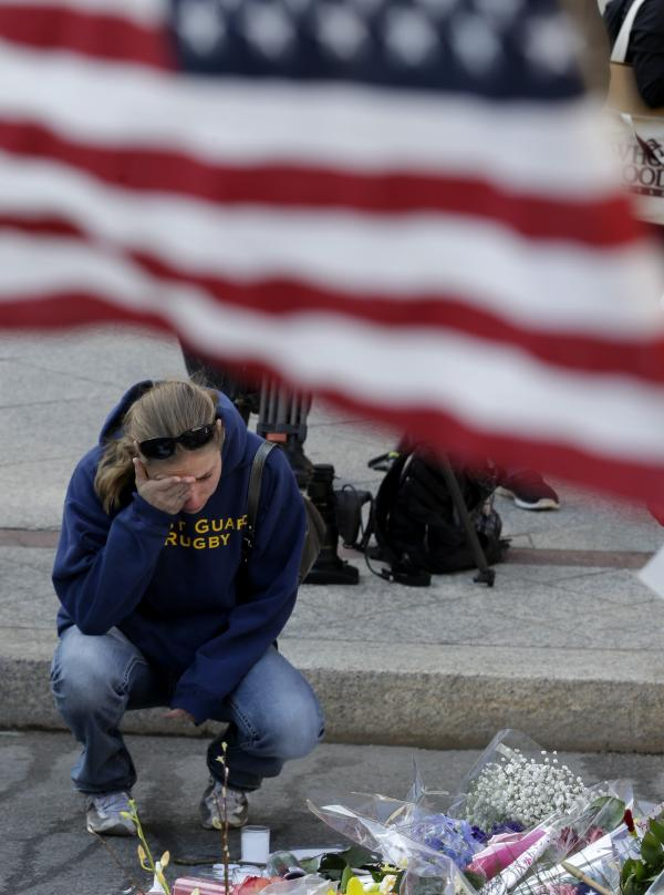 Jillian Blenis, 30, of Boston reacts while stopping at a makeshift memorial to marathon bombing victims Wednesday.