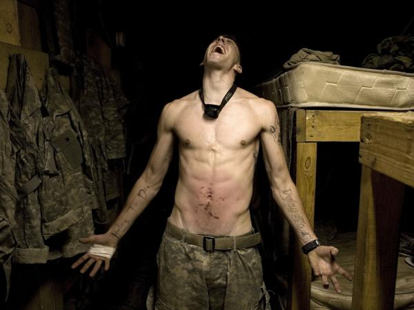 "Spc. Tad Donoho screams with pain in 2008 after being administered a ""pink belly"" for his birthday in Korengal Valley, Kunar province, Afghanistan. Each member of the platoon strikes his stomach until it begins to bruise, hence the name pink belly. From the book <em>Infidel</em>."
