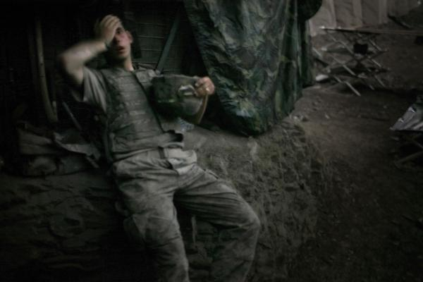 "A soldier rests at the end of a day of heavy fighting at the Restrepo outpost in Afghanistan's Korengal Valley. This image won the 2007 World Press Photo of the Year award. ""The funny thing about war, it actually almost never hardens people,"" Junger says. ""It almost always humanizes them, and I think war humanized Tim tremendously because it inflicted so much pain on him."""