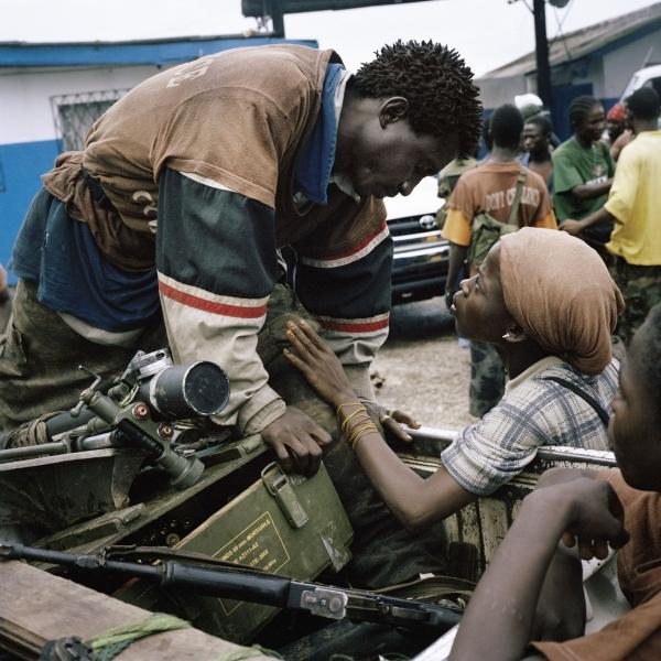 "An anti-aircraft brigade member exchanges a brief tender word with his girlfriend during heavy fighting in Monrovia in 2003. ""It's kind of an ugly environment ... and they're holding each other and they're looking at each other with just incredible love,"" Junger says. ""And it's just — the look on both of their faces is so beautiful, and that's what Tim was looking for in war reporting."""