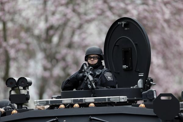 A police officer stands at alert in tactical gear in Watertown on Friday.