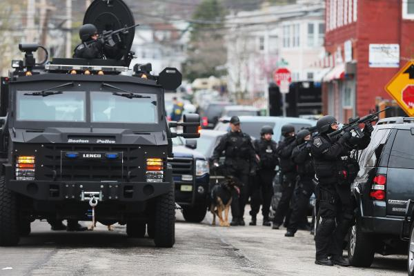 SWAT team members search for the remaining Boston Marathon bombing suspect at an apartment building. One of the two suspects died after a chase and shootout earlier Friday.