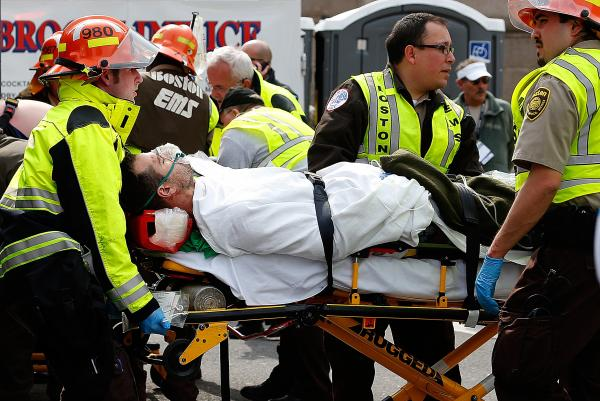 A man is loaded into an ambulance after he was injured by one of two bombs that exploded during the Boston Marathon on Monday.