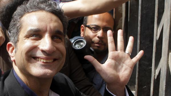 Egyptian satirist Bassem Youssef waves to his supporters as he enters Egypt's state prosecutor general's office in Cairo on March 31 to face charges of allegedly insulting Islam and the country's leader.