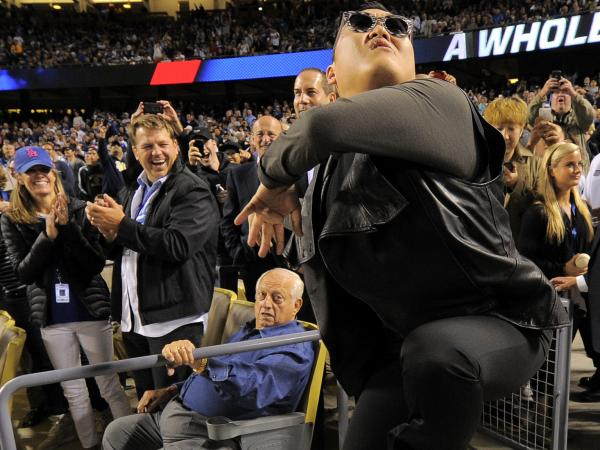 As PSY danced, former Dodgers manager Tommy Lasorda (sitting, in the blue shirt) looked on with a quizzical expression.