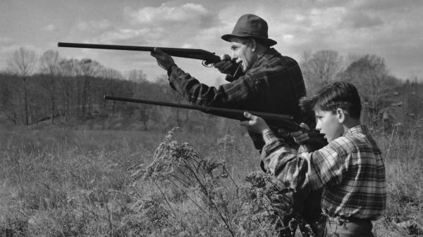 A man and a boy out hunting with shotguns, circa 1955.