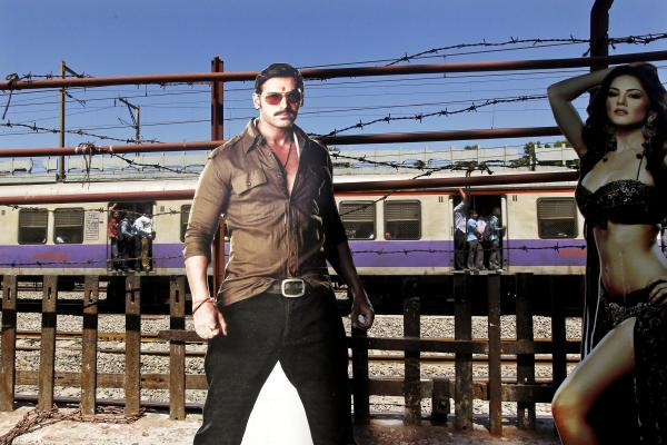 A train moves past a cutout of Bollywood actors John Abraham and Sunny Leone, outside a cinema hall in Mumbai. Four top Indian filmmakers have come together to make <em>Bombay Talkies</em>, a collection of short films that hits theaters on Friday.