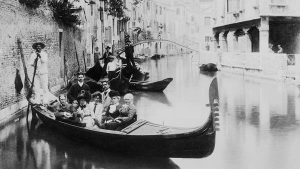 Gondolas have long played a part in the Venetian tourist experience. But as tourism has grown and the local population has declined, everyday gondolas called <em>traghetti </em>have all but disappeared. Above, a group of tourists poses on a canal, circa 1900.