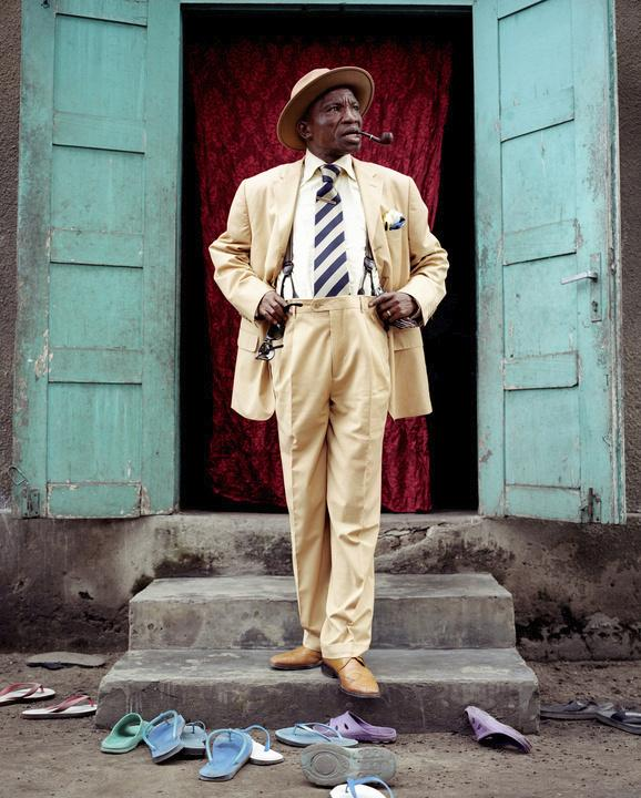 Severin Mouyengo, who has been a <em>sapeur</em> since the 1970s, poses in the entrance of his family house in the Bacongo neighborhood. Sandals on the ground are from his family members.