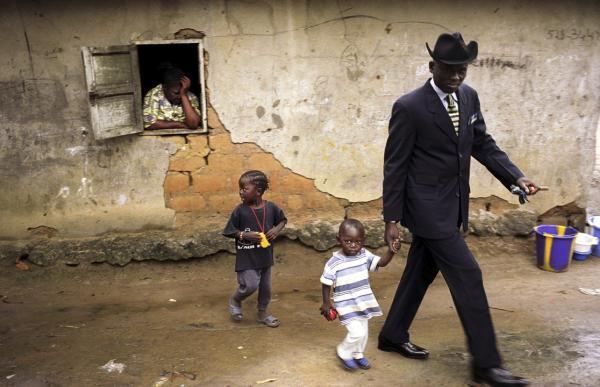 Willy Covari, one of the most admired <em>sapeurs</em> of the Bacongo neighborhood, walks with his two children in his plot.