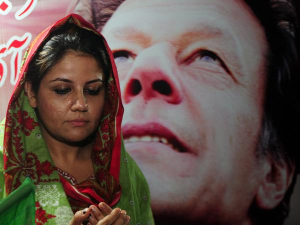 An Imran Khan supporter prays on Tuesday for his quick recovery after he was rushed to a hospital with head injuries.