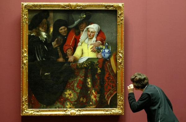 <em>The Procuress</em>, painted by Johannes Vermeer in 1656, hangs in a Dresden, Germany, museum in 2004. While this particular work is not in question, Benjamin Binstock argues that other pieces attributed to the Dutch master are by an apprentice and a member of his household.