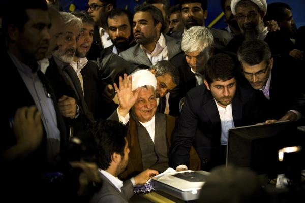 Former Iranian President Ali Akbar Hashemi Rafsanjani (center) waves as he registers his candidacy for the upcoming presidential election at the interior ministry in Tehran, May 11. Rafsanjani has been isolated since massive street protests in 2009 after the disputed re-election of President Mahmoud Ahmadinejad.