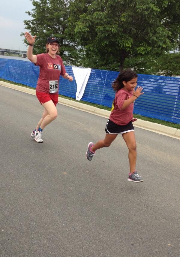 Waving to sideline supporters, <em>All Things Considered</em> Associate Producer and race Team Captain Justine Kenin is pictured here nearing the finish line with her daughter, Annie.