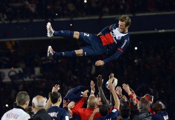 Paris Saint-Germain's English midfielder David Beckham is thrown in the air by teammates.