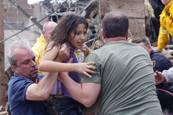 A child is pulled from the rubble of Plaza Towers Elementary School in Moore, Okla., on Monday, after a tornado as much as a mile wide with winds up to 200 mph roared through the Oklahoma City suburbs.