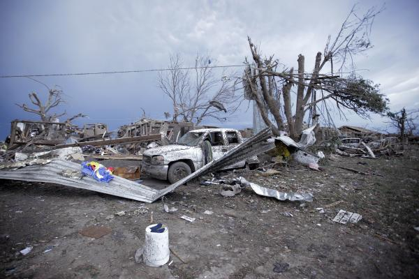 Piles of debris and cars lie around a home destroyed by a tornado in Moore, Oklahoma.