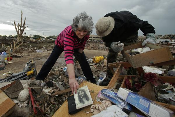 Lea Bessinger salvages a picture of Jesus as she and her son Josh Bessinger sort through the rubble of her home in Moore.