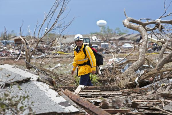 A rescue worker checks the rubble in a residential area of Moore, Okla., on Tuesday after a massive tornado struck the area Monday. Emergency workers pulled more than 100 survivors from the rubble of homes, schools and a hospital in Moore.