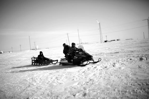 Local veterans representative Sean Komonaseak drives a snowmobile with Tommy Sowers (back seat) and Sean Foertsch across the ice to the village of Wales, Alaska.