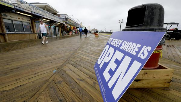 People walk on the boardwalk in Seaside Heights, N.J., on Friday. The Jersey Shore beaches officially opened for the summer, after rebuilding following the destruction left behind by Superstorm Sandy last fall. The storm caused $37 billion of damage in the state.