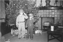 Walter Carter and his older brother salute their father, an Army doctor in World War II, in front of their Christmas tree in 1943.