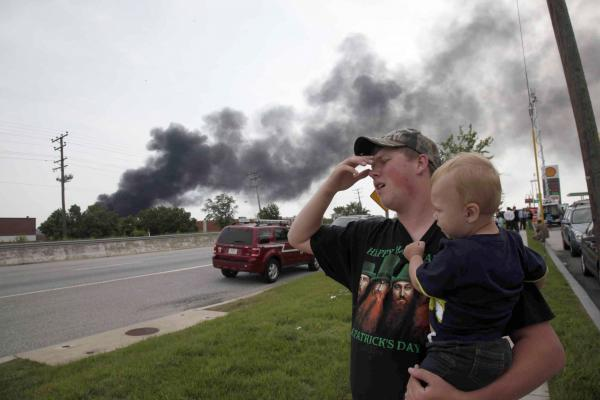 Mark Paugh carries his 15-month-old son Ryan as they watch smoke from a train derailment in White Marsh, Md. on Tuesday.