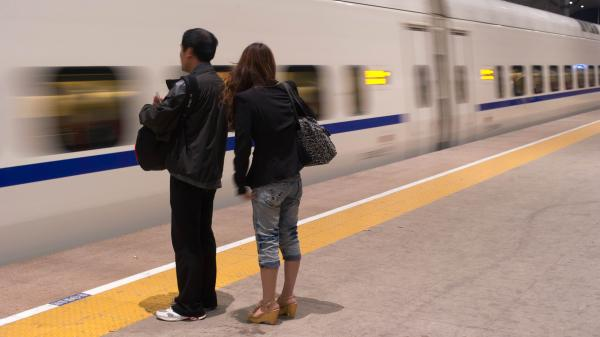 A couple waits for a high-speed train in the Chinese city of Qinhuangdao. Modern infrastructure and the expanding private sector have greatly increased efficiency and customer service in many parts of Chinese life.