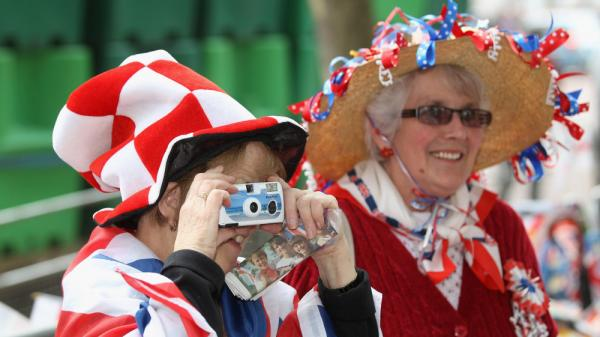 Fans of the royal family take photographs as they wait for the wedding of Prince William and Kate Middleton in London.