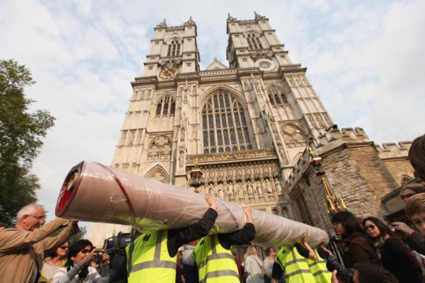 Workers carry in sections of the red carpet at Westminster Abbey, where Prince William and Kate Middleton are scheduled to get married Friday.