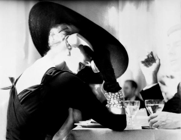Lillian Bassman's photograph <em>The V‐Back Evenings</em> shows model and actress Suzy Parker having a drink (and some fun) in 1955.