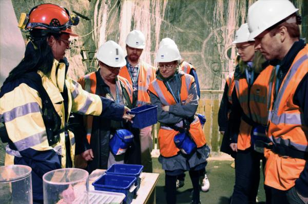As many as 10,000 people per year visit the underground Aspo Hard Rock Laboratory in Sweden — a test area for used nuclear fuel. Asa Nielsson (left) encourages visitors to the caverns to touch samples of clay that will be used to help seal canisters of the fuel.