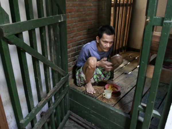 In this photo from 2006, Auzain, 38, a mental health patient, sits in a cage his family made for him at his home in Mibo on the outskirts of Banda Aceh, Indonesia. Auzain was one of more than 150 mentally ill people found chained, shackled or locked up in Aceh province after a decades-long civil war ended.