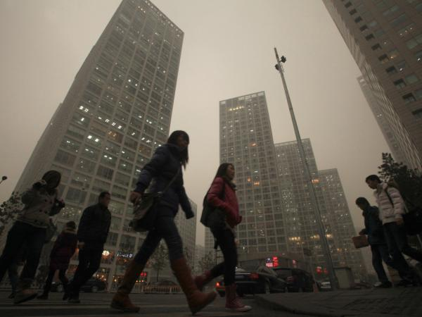 Chinese walk to work midday as heavy smog hangs over downtown Beijing.