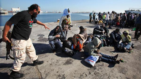 A Libyan security guard stands next to African immigrants in the port of Tripoli on Dec. 5, 2011, after authorities foiled their attempt to illegally immigrate to Europe. Thousands of sub-Saharan Africans have been stranded or imprisoned in Libya, suspected of being mercenaries for former Libyan dictator Moammar Gadhafi.