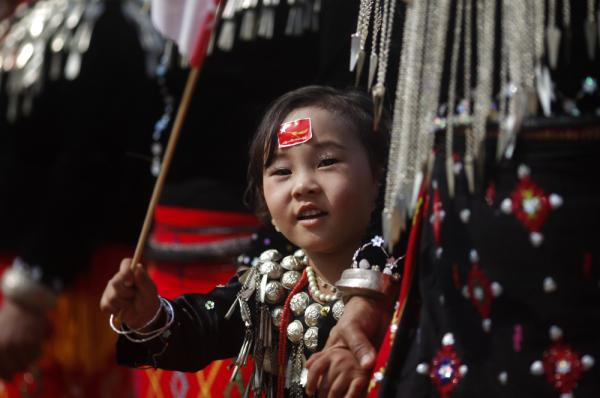 A girl from the Kachin ethnic group waves the flag of Suu Kyi's National League for Democracy as the democracy leader arrives in Namti village last week.