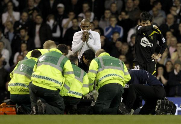 Bolton Wanderers' Fabrice Muamba is obscured by medical staff trying to resuscitate him after collapsing. His teammate Ryo Miyaichi, right, and Tottenham Hotspur's Jermain Defoe, center top, watch.