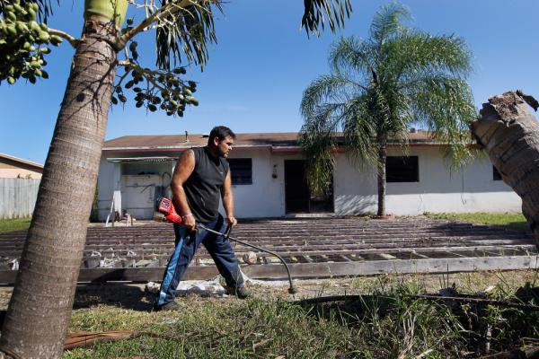 Renzo Salazar maintains the yard around a foreclosed house in Miami after the bank hired him to keep the home from falling into complete dilapidation.