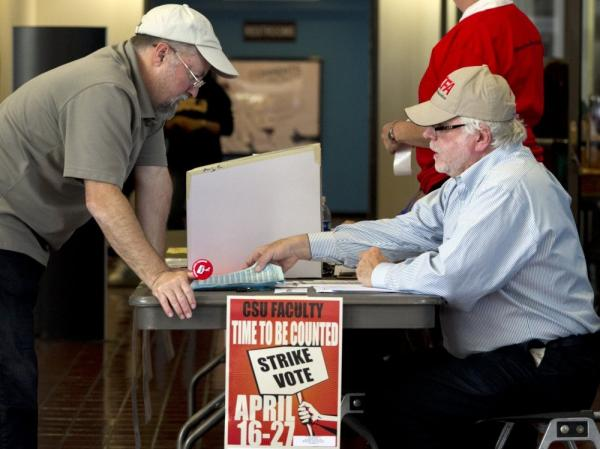 California Faculty Association Vice President Douglas Domingo-Foraste (right) helps Cal State, Long Beach, professor Mark Sugars vote last month on whether to authorize a strike. The strike was authorized Wednesday.